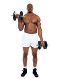 Hombre muscular que ejercita con pesas de gimnasia Imagen de archivo libre de regalías