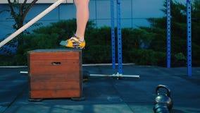 Hombre muscular que entrena a las piernas y al salto en la caja de madera metrajes