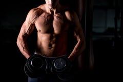 Hombre muscular que hace ejercicios con pesas de gimnasia en centro de aptitud Fotografía de archivo libre de regalías
