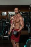 Hombre muscular que hace el ejercicio pesado para el bíceps Imagenes de archivo