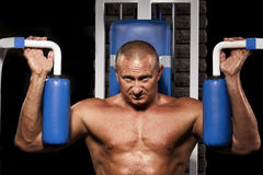 Hombre muscular que hace levantamiento de pesas en gimnasia Imágenes de archivo libres de regalías