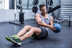 Hombre muscular que hace los ejercicios rusos de la torsión Fotos de archivo