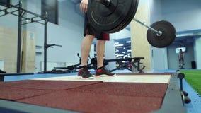 Hombre muscular que lanza el barbell pesado en el entrenamiento del piso en gimnasio en la cámara lenta almacen de metraje de vídeo