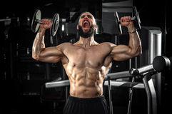Hombre muscular que levanta algunas pesas de gimnasia foto de archivo