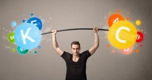 Hombre muscular que levanta pesos coloridos de la vitamina Fotografía de archivo