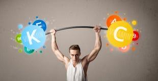 Hombre muscular que levanta pesos coloridos de la vitamina Foto de archivo