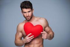 Hombre muscular que lleva a cabo forma del corazón Fotos de archivo libres de regalías