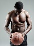 Hombre muscular que lleva a cabo un baloncesto fotografía de archivo libre de regalías
