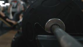 Hombre muscular que pone las láminas pesadas en barbell vídeo de la cámara lenta almacen de video
