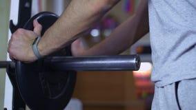 Hombre muscular que pone las láminas pesadas en barbell y que levanta en gimnasio almacen de metraje de vídeo
