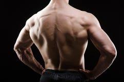 Hombre muscular que presenta en estudio oscuro imagen de archivo