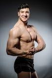 Hombre muscular que presenta en estudio oscuro fotos de archivo