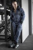 Hombre muscular que presenta en gimnasio fotografía de archivo libre de regalías