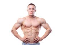 Hombre muscular que presenta sobre fondo aislado blanco Imagen de archivo libre de regalías