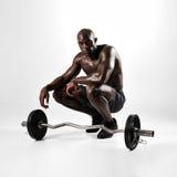 Hombre muscular que se agacha con el barbell foto de archivo