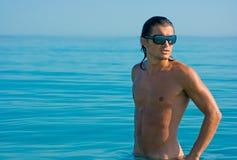 Hombre muscular que se coloca en agua imagenes de archivo