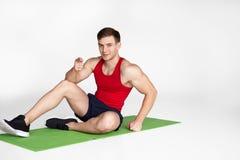 Hombre muscular que se sienta en la estera foto de archivo libre de regalías