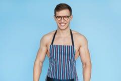 Hombre muscular sonriente en delantal imagenes de archivo