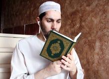 Hombre musulmán árabe con el libro sagrado y las auriculares islámicos del Corán fotografía de archivo