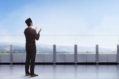 Hombre musulmán asiático joven que ruega con el aumento de la mano en el balcón Foto de archivo
