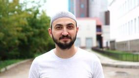 Hombre musulmán barbudo en la ciudad que mira la cámara metrajes