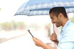 Hombre musulmán que lee una tableta debajo de la lluvia imagen de archivo