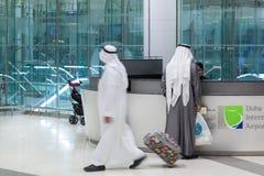 Hombre musulmán que lleva la ropa tradicional en el mostrador de información en Doha Imágenes de archivo libres de regalías
