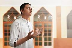 Hombre musulmán que ruega la mezquita interior Foto de archivo libre de regalías