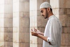 Hombre musulmán que ruega la mezquita interior Foto de archivo
