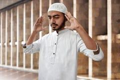 Hombre musulmán que ruega la mezquita interior Imagenes de archivo
