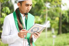 Hombre musulmán que sostiene Al-Quran Foto de archivo libre de regalías
