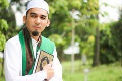 Hombre musulmán que sostiene Al-Quran Imagenes de archivo