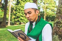 Hombre musulmán que sostiene Al-Quran Fotos de archivo