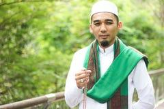 Hombre musulmán sonriente que sostiene Tasbih Imagen de archivo libre de regalías