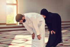 Hombre musulmán y mujer que ruegan en mezquita Imagen de archivo libre de regalías