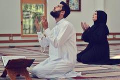 Hombre musulmán y mujer que ruegan en mezquita Fotografía de archivo