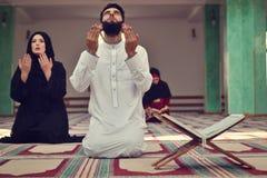 Hombre musulmán y mujer que ruegan en mezquita Foto de archivo