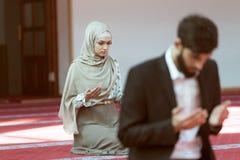 Hombre musulmán y mujer que ruegan en mezquita Imagenes de archivo
