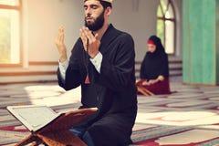 Hombre musulmán y mujer que ruegan para Alá en la mezquita junto Fotos de archivo libres de regalías