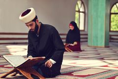 Hombre musulmán y mujer que ruegan para Alá en la mezquita junto Foto de archivo