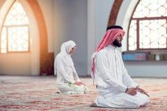 Hombre musulmán y mujer que ruegan para Alá en la mezquita junto Imagen de archivo