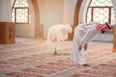 Hombre musulmán y mujer que ruegan para Alá en la mezquita junto Fotografía de archivo