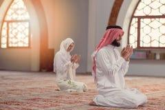 Hombre musulmán y mujer que ruegan para Alá en la mezquita junto Imagenes de archivo