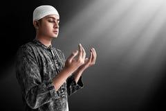 Hombre musulm?n asi?tico religioso que ruega fotografía de archivo libre de regalías