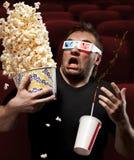 Hombre muy asustado que mira la película 3D Fotografía de archivo