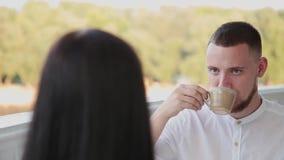 Hombre muy hermoso y atractivo que se sienta en un café para una taza de café almacen de video