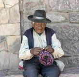 Hombre nativo peruano que hace punto un sombrero Imagenes de archivo