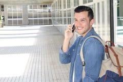 Hombre natural de mirada real joven que habla en su teléfono móvil para recibir buenas noticias con el espacio de la copia imagen de archivo libre de regalías