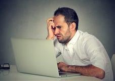 Hombre negativo que usa el ordenador portátil en cólera imagenes de archivo