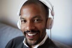 Hombre negro africano feliz que escucha la música que se relaja en el sofá del sofá con el teléfono celular móvil en la sala de e fotografía de archivo libre de regalías